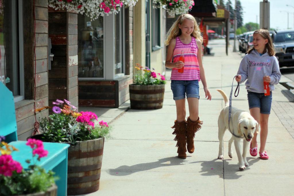 2 girls walking their dog in walker